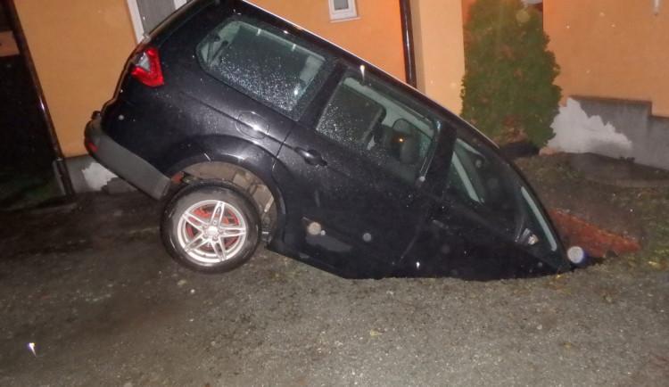 FOTO: Kuriózní nehoda. Pod autem se propadla zem a vozidlo zapadlo do jímky